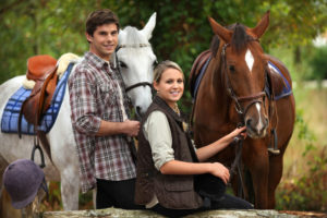 Smiling young couple holding the reins of beautiful horses in Helen GA